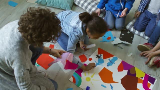 vídeos y material grabado en eventos de stock de crear collage de papel de colores con la maestra de preescolar - pegajoso