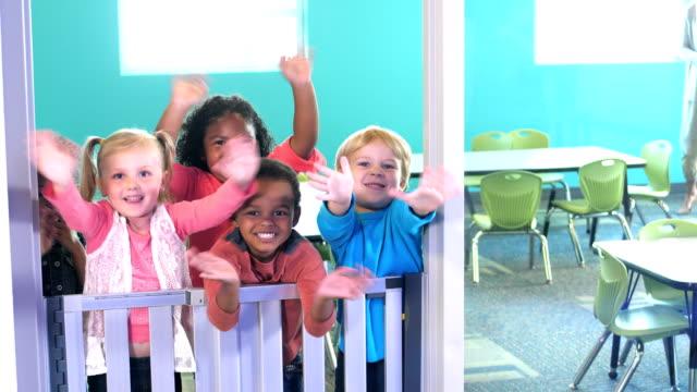 förskolebarn i klassen köra upp till dörröppningen, vajande - förskoleelev bildbanksvideor och videomaterial från bakom kulisserna