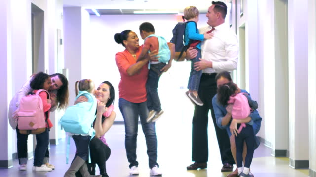Preschoolers in hallway running toward parents A multi-ethnic group of preschool children in a school hallway, run excitedly toward their parents who bend down and hug them. Some pick them up. The boys and girls are 4 years old child care stock videos & royalty-free footage