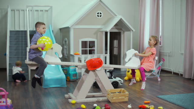 Preschoolers Riding Swing in Messy Nursery Preschoolers Riding Swing in Messy Nursery while Cute Infant Girl Crawling on the Background. Concept of Childhood and Educational Games cousin stock videos & royalty-free footage