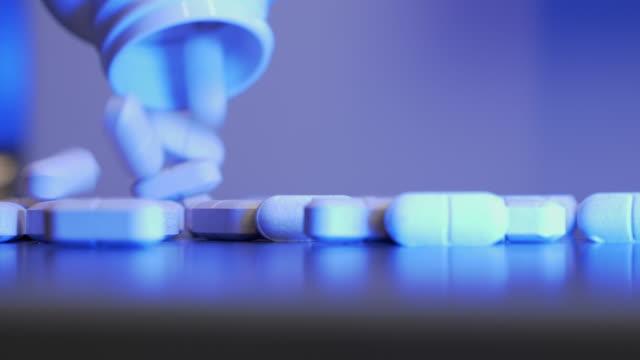 reçeteli şişe siyah masaya dökülen beyaz haplarla dolu. tıp endüstrisi. kişi beyaz plastik konteyner dışarı masada birçok farklı hap düşüyor. farmakotik üretim - doping stok videoları ve detay görüntü çekimi