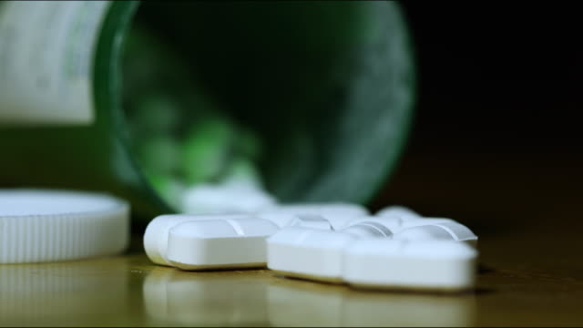 Prescription Medication Ominous Lighting A 4K macro video clip of prescription painkillers with ominous lighting moving above them. narcotic stock videos & royalty-free footage