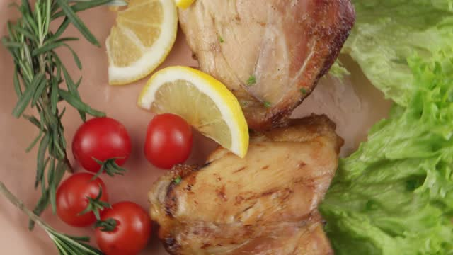 Presentation of decoration of the baked chicken thighs and a garnish with cherry tomatoes, lettuce and a lemon with sprig of rosemary