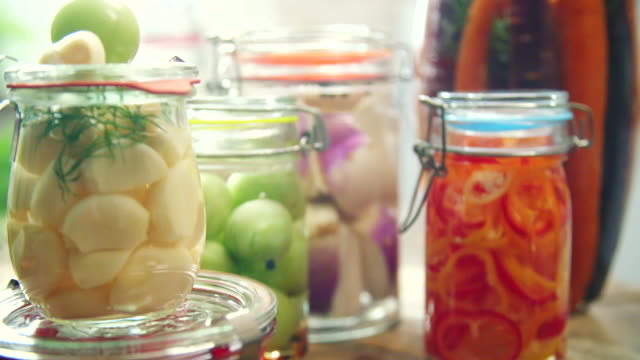 Preserving Organic Vegetables in Jars Preserving organic vegetables in jars like carrots, cucumbers, tomatoes, chilis, paprika and radishes. pickle stock videos & royalty-free footage