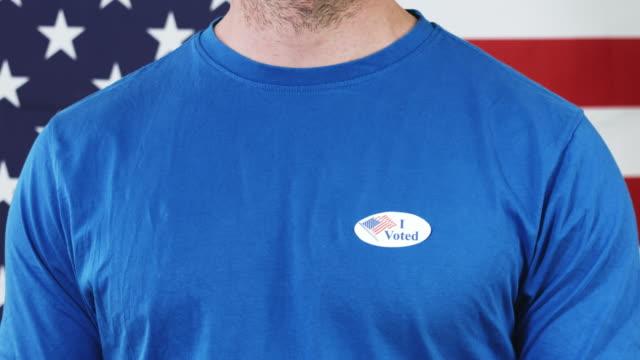 präsidentenwahl-aufkleber auf einem mann - aufkleber stock-videos und b-roll-filmmaterial