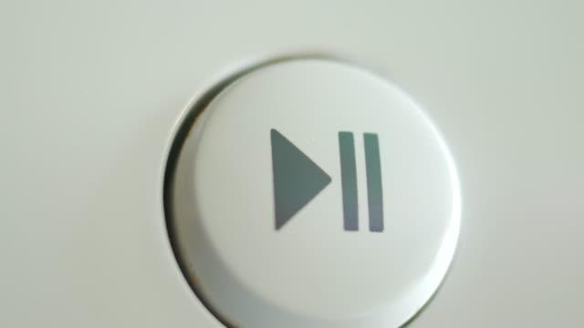 premere il pulsante riproduci pausa sul dispositivo - spingere video stock e b–roll