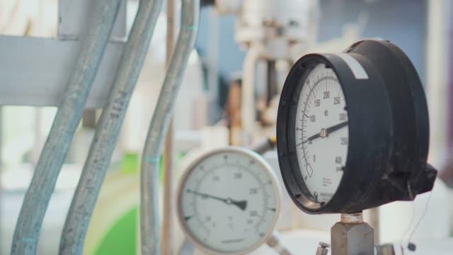 pressure gauge and steel pipeline at industrial plant - замороженные продукты стоковые видео и кадры b-roll