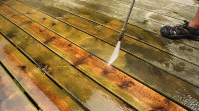Hochdruckreiniger gereinigt einen verwitterten Deck – Video
