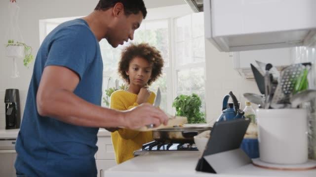 vidéos et rushes de fille noire pré-adolescente et son père préparant la nourriture suivant une recette sur un ordinateur de tablette, fermez vers le haut - recette