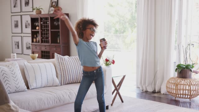pre-teen black girl dancing and singing at home using phone as a microphone, three quarter length - preadolescente video stock e b–roll