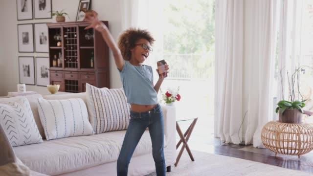 ön-teen siyah kız dans ve evde şarkı bir mikrofon olarak telefon kullanarak, üç çeyrek uzunluğu - dijital yerli stok videoları ve detay görüntü çekimi