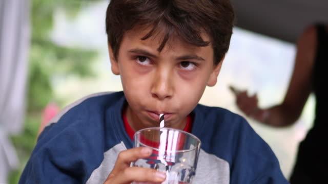 preteen boy drinking juice with straw - solo un bambino maschio video stock e b–roll