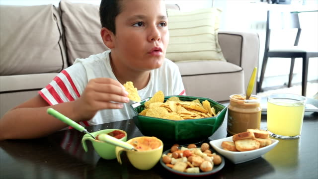 Preteen boy eating unhealthy eating video
