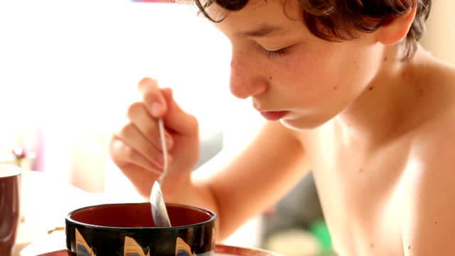 Pre-teen boy playing with and then eating bowl of cereal video