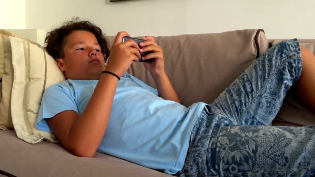Preteen boy using smartphone Preteen boy laying sofa with smartphone texting message or playing game at home. Technology, internet communication and people concept one boy only stock videos & royalty-free footage