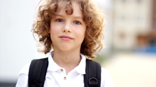preteen curly blue-eyed boy laughing and looking at camera. the schoolboy is dressed in a white shirt and carries a satchel. school holidays, back to school, happy schoolboy - scolaro video stock e b–roll