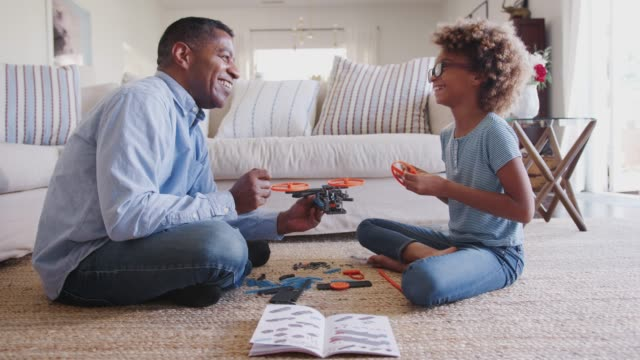 Pre-teen girl and grandad sitting on the floor constructing a toy, looking at each other, side view Pre-teen girl and grandad sitting on the floor constructing a toy, looking at each other, side view granddaughter stock videos & royalty-free footage