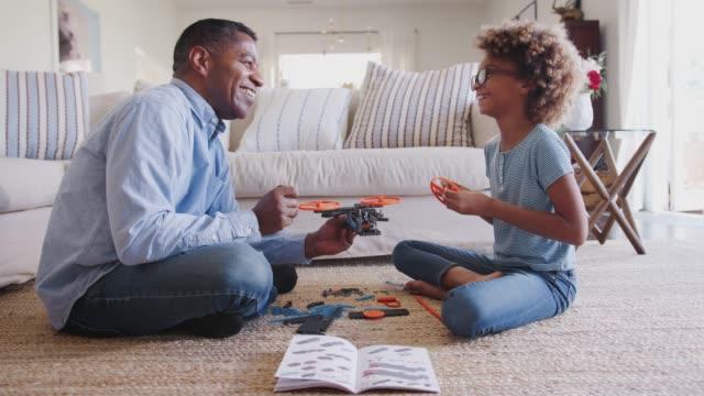 ragazza pre-adolescente e nonno seduti sul pavimento a costruire un giocattolo, guardandosi l'un l'altro, vista laterale - nipote femmina video stock e b–roll