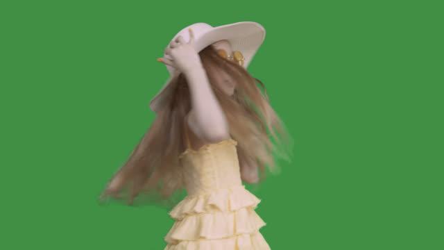黄色のドレスと帽子をかぶったプレティーンの女の子は、歌う、アルファチャンネルを踊っています。 - 空白点の映像素材/bロール