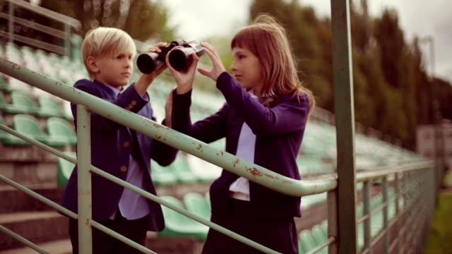 preteen girl looking away through binoculars, brother nearby, profile - fianco a fianco video stock e b–roll