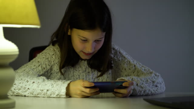 karanlık odada akıllı telefonda online oyun oynayan pre-teen kız - dijital yerli stok videoları ve detay görüntü çekimi