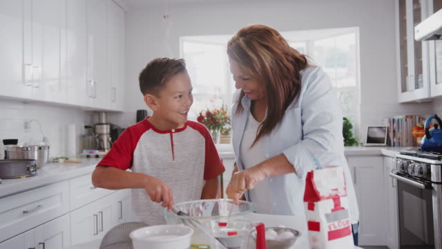 Pre-teen Hispanic boy and his grandmother making cakes in the kitchen, mixing cake mix, close up Pre-teen Hispanic boy and his grandmother making cakes in the kitchen, mixing cake mix, close up mixing bowl stock videos & royalty-free footage