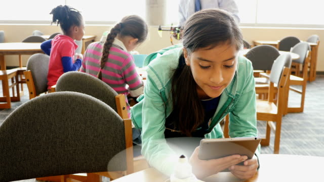 Pre-teen Hispanic female student uses digital tablet to control robotic helicopter in STEM school library video