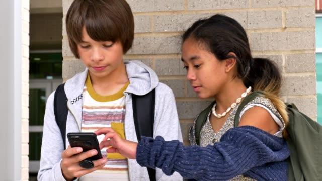 preteen junior high students use smartphone on the school campus - предподростковый возраст стоковые видео и кадры b-roll