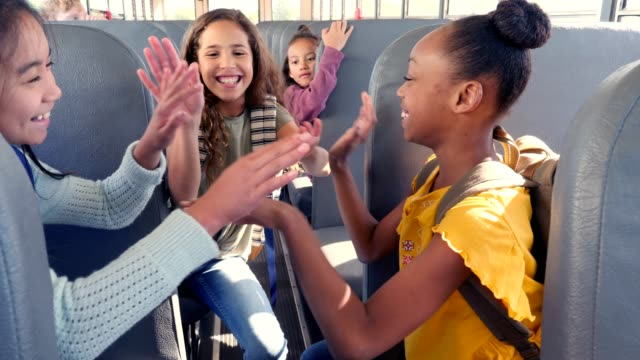 preteen school girls play hand clapping game on school bus - school buses stock videos and b-roll footage
