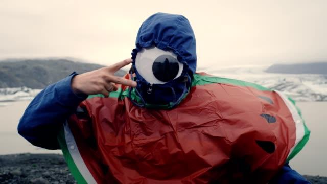 pretending to be a cyclops. man having fun at glacier lagoon - gente serena video stock e b–roll