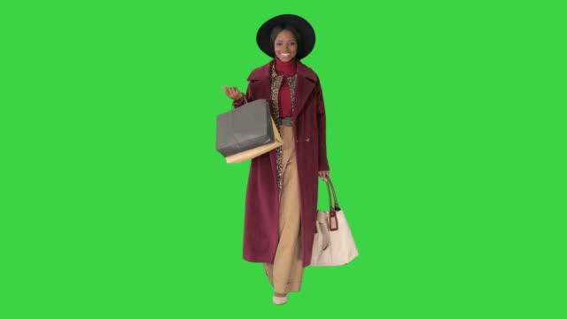vídeos y material grabado en eventos de stock de bonita chica de moda afroamericana en abrigo y sombrero negro paseando con bolsas de compras en una pantalla verde, chroma key - abrigo