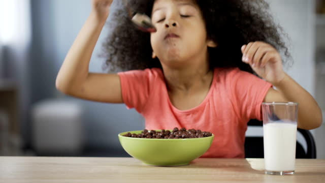 Pretty African American girl eating cornflakes with appetite and drinking milk Pretty African American girl eating cornflakes with appetite and drinking milk hungry child stock videos & royalty-free footage
