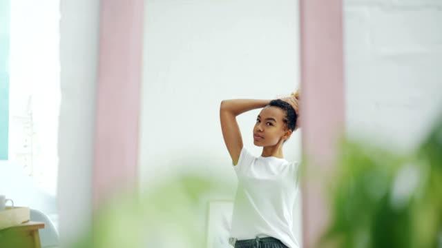 vidéos et rushes de fille assez afro-américaine est la fixation de ses cheveux bouclé, regarder dans le miroir à la maison et le sourire. belles personnes, concept de mode de vie et les intérieurs jeunes. - soins capillaires