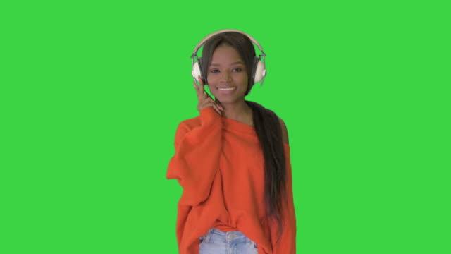 yeşil ekranda müzik zevk kameraya yürüyen kulaklık ile pretty afro-amerikan kadın, chroma key - kompozisyon stok videoları ve detay görüntü çekimi