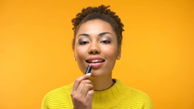 hübsches afroamerikanische mädchen auftragen von lippenstift und zwinkert, bereit für datum - lippenstift stock-videos und b-roll-filmmaterial