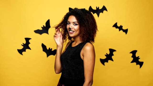 Pretty afro american lady with cat make-up and ears laughing and flirting to camera isolated over yellow wall with bats video