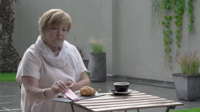 Une femme assez âgée est manger un croissant et boire du thé. Elle s'asseoir sur la terrasse. Il pleut. - Vidéo