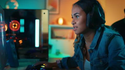vidéos et rushes de jolie et excité de black girl gamer dans les écouteurs est jouer first-person shooter jeu vidéo en ligne sur son ordinateur. chambre et pc ont coloré néons led. agréable soirée à la maison. - petites filles