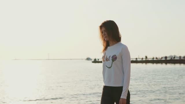 hübsche und junge frau alleine spaziergänge am strand, blick auf das meer und wasser - introspektion stock-videos und b-roll-filmmaterial