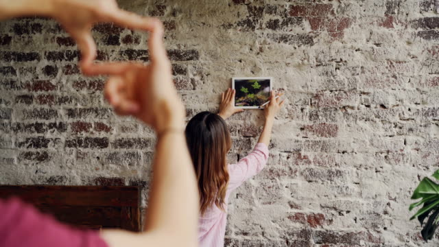 Pretty asian woman is choosing place for framed photograph on brick wall while her boyfriend is making frame shape with his fingers and looking at her, hands in foreground. Pretty asian woman is choosing place for framed photograph on brick wall while her boyfriend is making frame shape with his fingers and looking at her, male hands in foreground. loft apartment stock videos & royalty-free footage