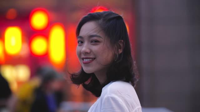 pretty asian young woman smile at camera at night - chińczycy filmów i materiałów b-roll