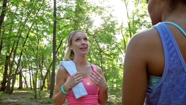 pretty athletic woman talking with friend before exercising or running outdoors - black woman towel workout bildbanksvideor och videomaterial från bakom kulisserna