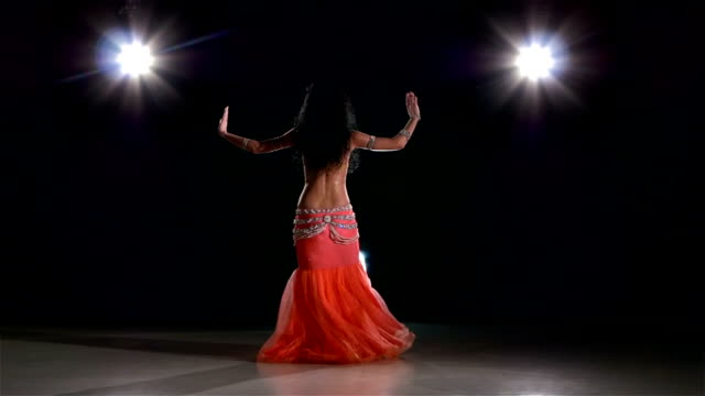 Pretty belly dance woman bellydancer dancing on black, back light, slow motion