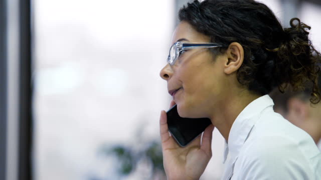 Pretty biracial woman talking on cellphone, persuading client to make a purchase video