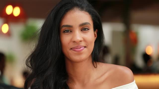 hübsche schwarze afrikanische amerikanische junge frau lächelnd vor der kamera - attraktive frau stock-videos und b-roll-filmmaterial