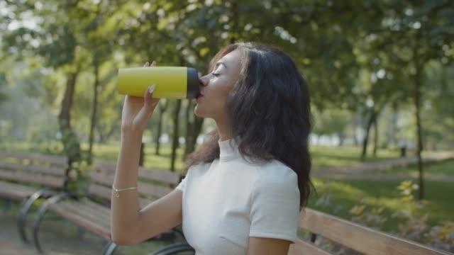 Pretty black female drinking coffee outdoors
