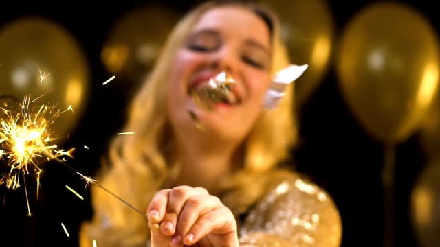 vídeos y material grabado en eventos de stock de bonita rubia agitando luz de bengala bajo confeti cayendo en la fiesta, el baile - baile de estudiantes de secundaria