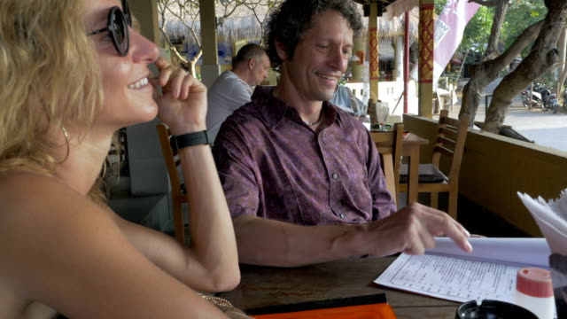 A pretty blond woman and handsome man look over a menu in outdoor cafe A young, thin, blond woman twirls her hair while a man looks over a menu in an outdoor cafe or restaurant in a warm tropical setting. sideways glance stock videos & royalty-free footage