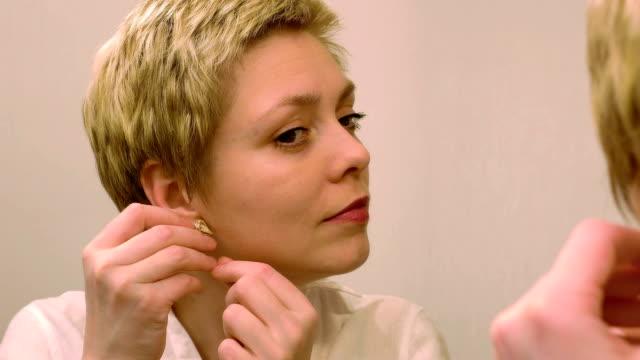 Pretty blond woman wears earrings and smartens up video