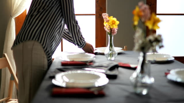 Pretty blonde Caucasian woman setting up table for lunch